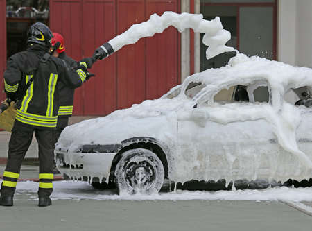 extinguish: firemen during exercise to extinguish a fire in a car with foam