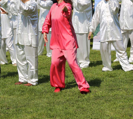 taiji: Tai Chi martial art Woman with pink silk dress perfectly perform the exercises in the large public park Stock Photo