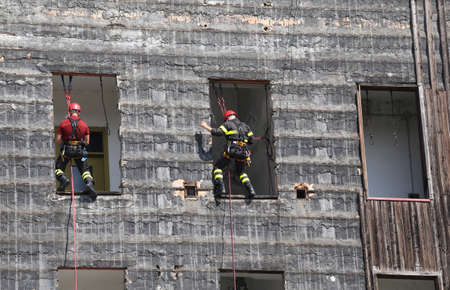 abseiling: two bold and daring climbers of firefighters climbing a wall of an house