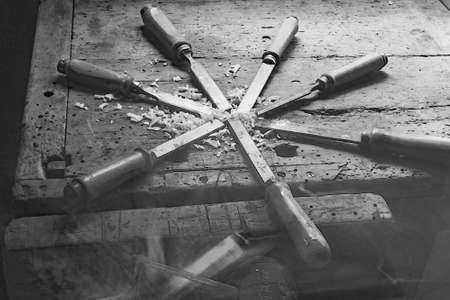 chisels: series of many sharp steel blades many chisels and sawdust chippings in Workbench in black and white Stock Photo