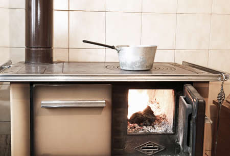 woodburning: ancient wood-burning stove in the kitchen of mountain home
