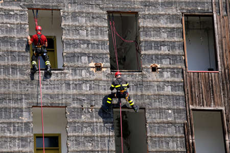 rappel: two climbers of firefighters climbing a wall of a house during the fire drill Stock Photo