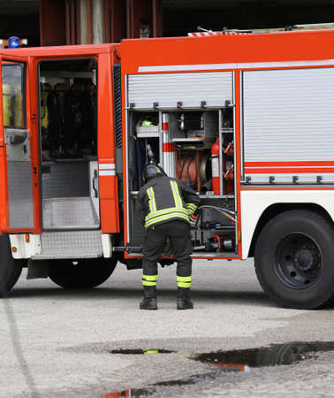 fire brigade: Firefighter prepares the water hoses to put out the fire during a training exercise in fire brigade station Stock Photo