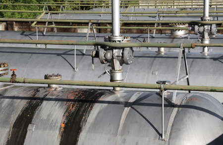 benzene: many steel safety valves over the container under full pressure of flammable gas Stock Photo