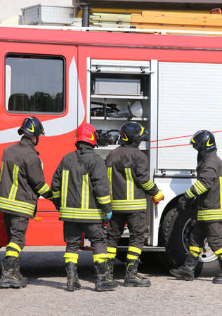 fire brigade: brave firefighters with fire engine truck during an exercise in fire brigade station Stock Photo