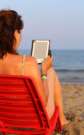 technologically: young woman  reads the ebook on the beach in summer Stock Photo