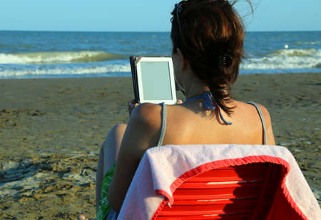 Pretty woman on red chair reads the ebook on the beach by the woman reads the ebook on the beach by the sea in summer photo fandeluxe Ebook collections