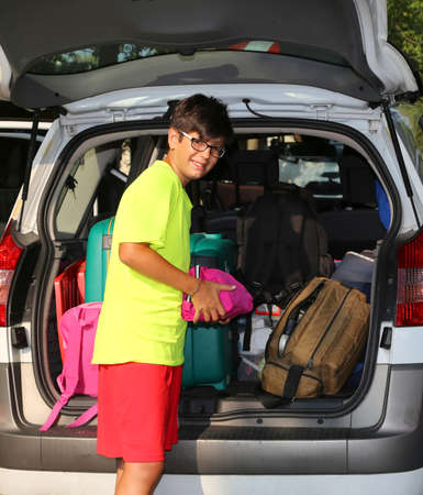 return trip: young boy with glasses loaded the luggage in the trunk of the car during the trip of the summer holidays