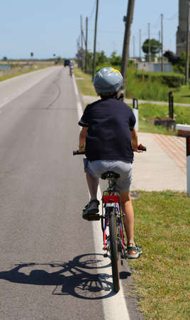 hayride: Kid riding a bicycle with the protective helmet along the paved road Stock Photo