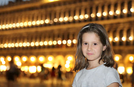 a nocturne: cute smiling little girl with the background of a Venetian Palace at night with the lights on