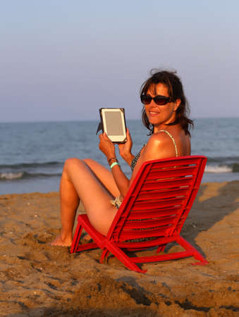 technologically: beautiful woman on Red Chair reads the ebook on the beach by the sea in summer Stock Photo