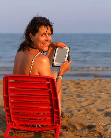 Pretty woman on red chair reads the ebook on the beach by the smiling woman reads the ebook on the beach photo fandeluxe Ebook collections