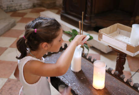 religiosity: cute little girl lights a candle wax into the Church and say a prayer