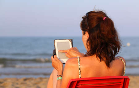 Pretty woman on red chair reads the ebook on the beach by the beautiful woman on chair reads the ebook on the beach photo fandeluxe Ebook collections