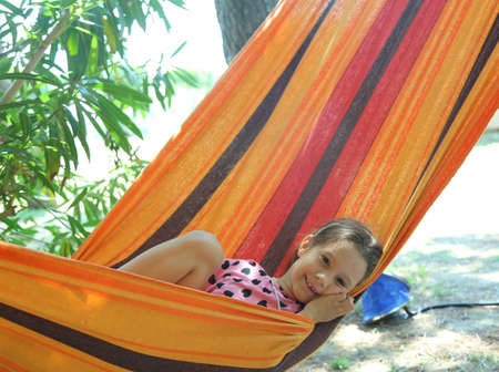 kiddy: smiling little girl rests in a hammock of the tourist village during the summer holidays