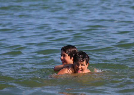 hermanos jugando: two young brothers playing in the water of the sea during the summer holidays
