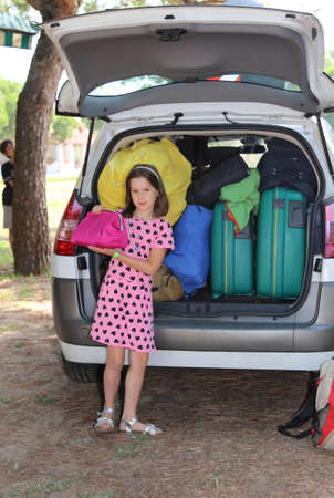 loads: little girl in pink dress loads the car during the summer holidays Stock Photo