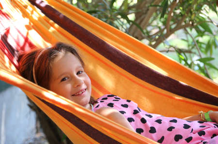 kiddy: smiling pretty baby rests in a hammock of the tourist village Stock Photo