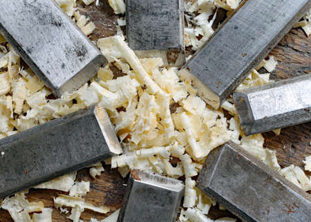 gouge: series of many sharp steel blades many chisels and sawdust chippings in Workbench Stock Photo