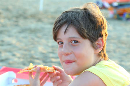 kiddy: hungry kid eats italian pizza with mozzarella cheese and fries on the shore of the beach in summer Stock Photo