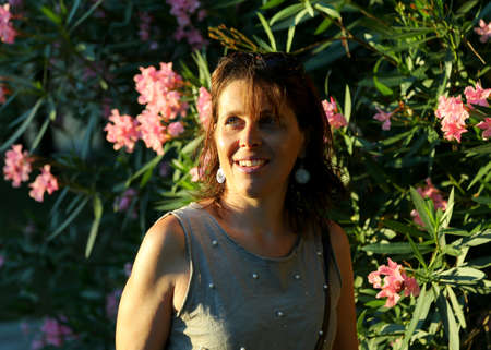 spaniard: cute smiling woman at sunset and oleander flowers in the background Stock Photo