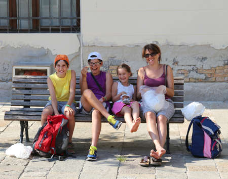 mother on bench: Happy family with a mother and three children laughing on the bench in the city