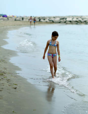 waterline: thoughtful little girl in swimsuit on the shore of the sea in summer