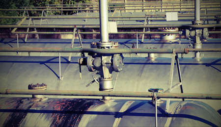 propane gas: large pipes and safety valve over the gigantic tank for storage of the propane gas in the industrial plant