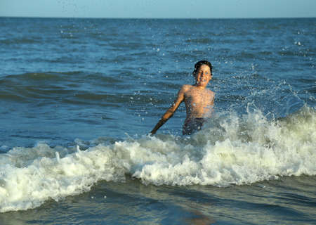 choppy: happy young boy plays by jumping the waves of the sea Stock Photo