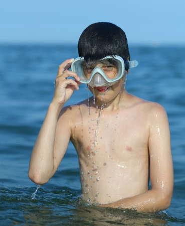 kiddy: Caucasian child has fun with the diver mask in the sea