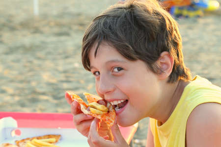 hungry kid: hungry kid eats pizza with mozzarella cheese and fries on the shore of the beach in summer Stock Photo
