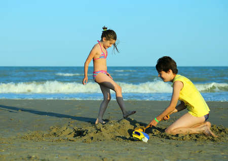 kiddy: lovely little girl and her brother play with sand in the beach in summer