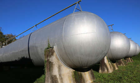 methane: many giant pressure vessels for the storage of flammable natural gas in the restricted area Stock Photo