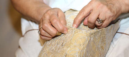 needle lace: elderly while embroidering a lace with lace pillow in Italy