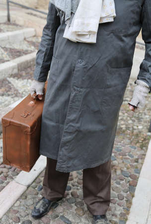 poorness: poor immigrant with old leather suitcase and filthy dress