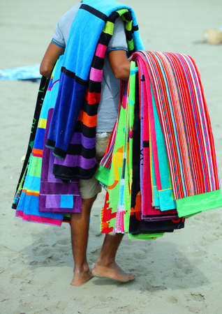 pedlar of cloth and towels on the beach in summer