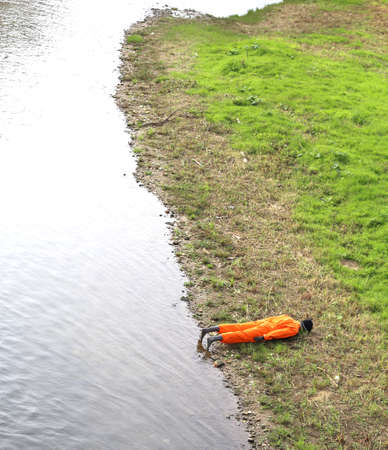 dummy with orange jumpsuit on the river bank during a training exercise of civil protection Stock Photo