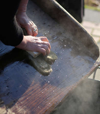 Hands of the elderly woman washing in the old wooden board