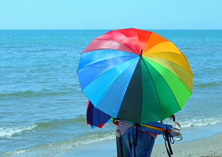 clandestine: african peddler of umbrellas on the beach in summer