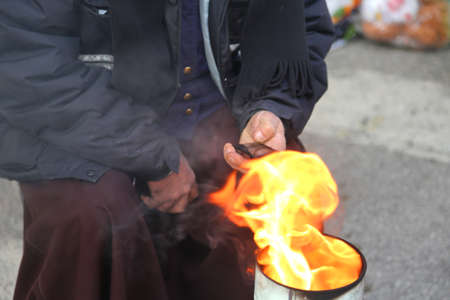 marginalized: poor man in the street using a mobile phone and heats up with the bonfire inside a bin