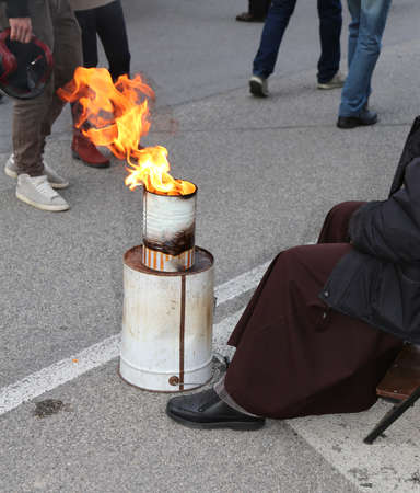 warms: poor friar with brown frock warms up in front of the bonfire in a bin in the street