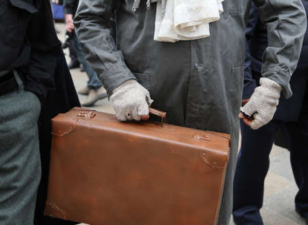 immigrant with old leather suitcase during the trip abroad in the field of humanitarian refugee reception