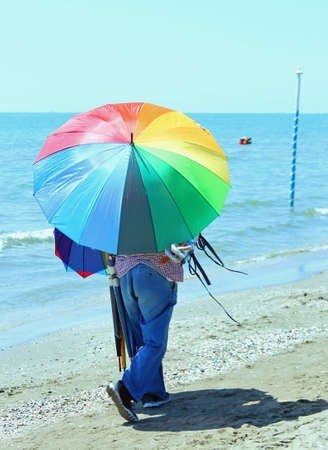 clandestine: poor peddler of colored umbrellas on the beach in summer