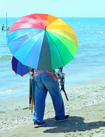 clandestine: poor peddler of umbrellas on the beach in summer