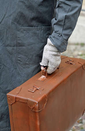 emigrant: poor emigrated with old leather suitcase and the broken glove during travel abroad