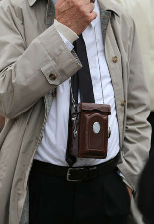 impermeable: photojournalist with antique camera and vintage clothes Stock Photo