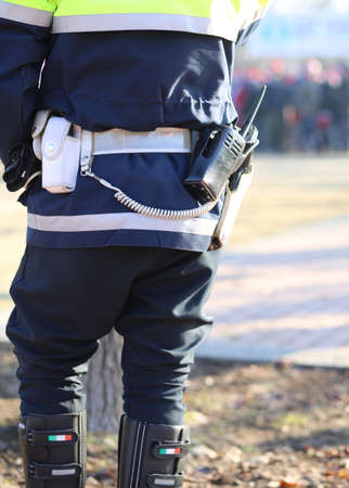 watchman: italian policeman in uniform with a radio transmitter and gun during a demonstration of the protesters