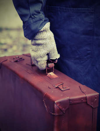 marginalized: poor person with the old worn leather suitcase Stock Photo