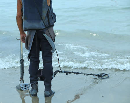 searcher: Man with metal detector  to find lost objects under the sand of the sea