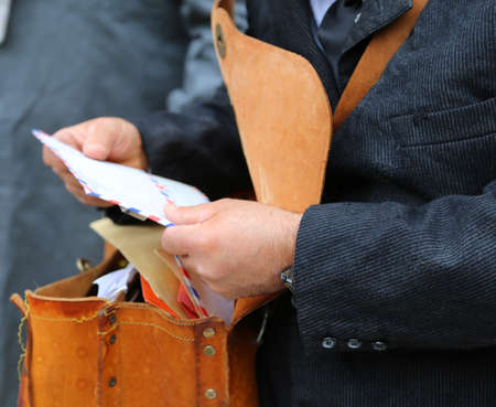 missive: postman with the old bag full of letters while delivering mail in the city